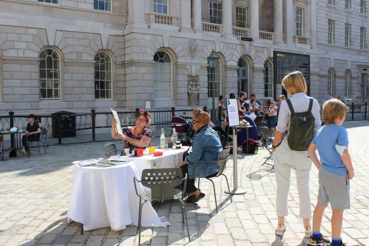 People sitting at and standing around a table in courtyard. An artist shows a drawing to a person. There are an arrivals board and more people in the background.