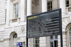 Analogue Departures board in a courtyard showing a list of names and dates
