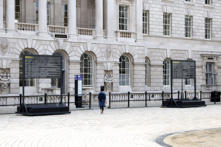 Two boards, one 'arrivals' and one 'departures' are situated in the Somerset House courtyard. a person walks in between them