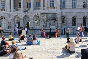 Two people sit with microphones in front of a 'Departures' board at Somerset House