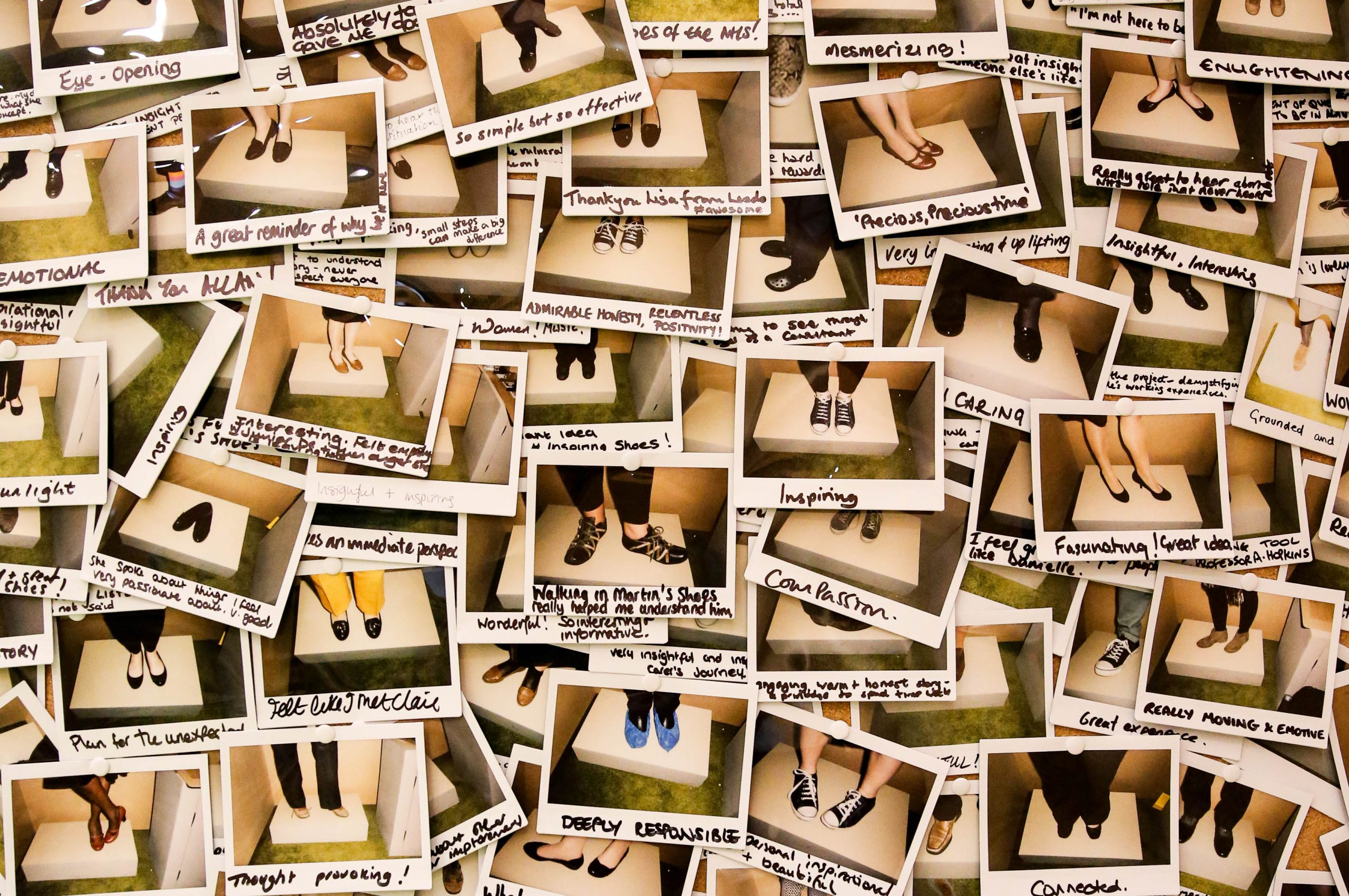 Mass of poloroid photos of feet in shoes, with handwritten audience messages