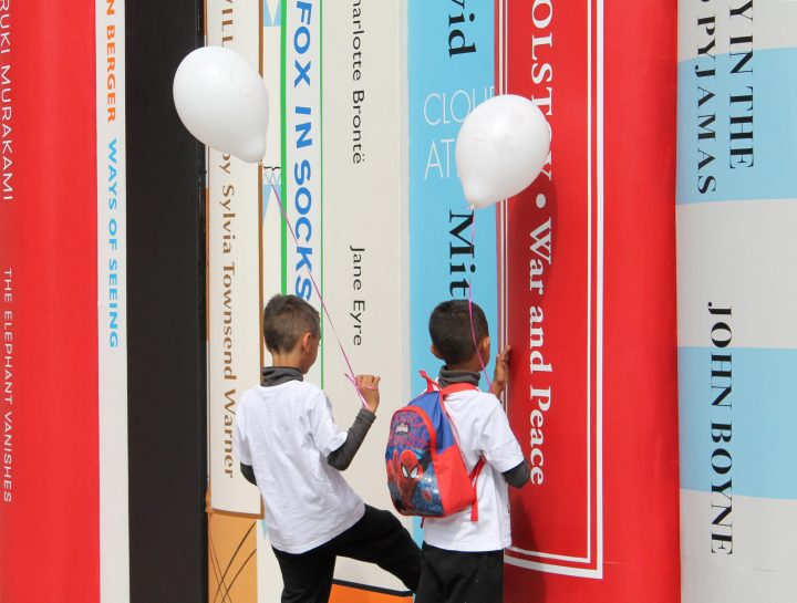 Two children with balloons in front of an oversized book installation