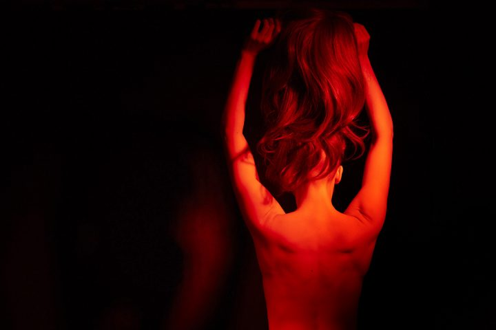 Naked person in dark space lit with red light. Their back is turned, their arms are in the air and they're holding a wig of long hair