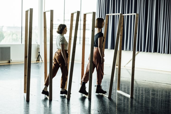 Two figures move through a series of sculptural spaces