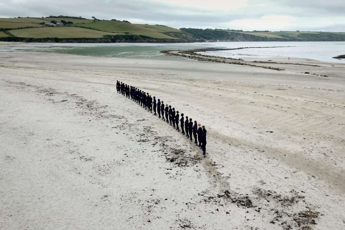 Choreographed line of performers on an empty beach
