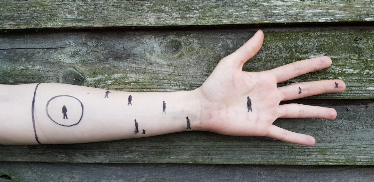 Person's arm stretched out against wooden fence background. There are pen drawings of stick people walking across their arm.