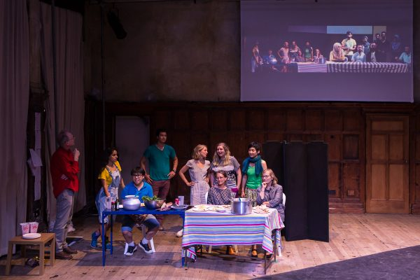 10 people on a stage, 5 gathered around a table, 2 cooking food, a projection of a similar scene in Gaza is on the screen behind