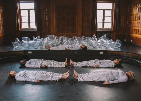 People dressing in matching white outfits lying on the floor of a studio with plastic bags filled with air