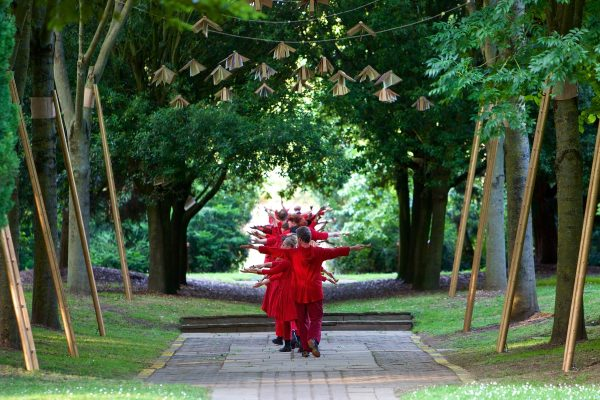 dancers in red walking along a path surrounded by trees