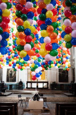 hundreds of ballons tied to a person lying down in a church