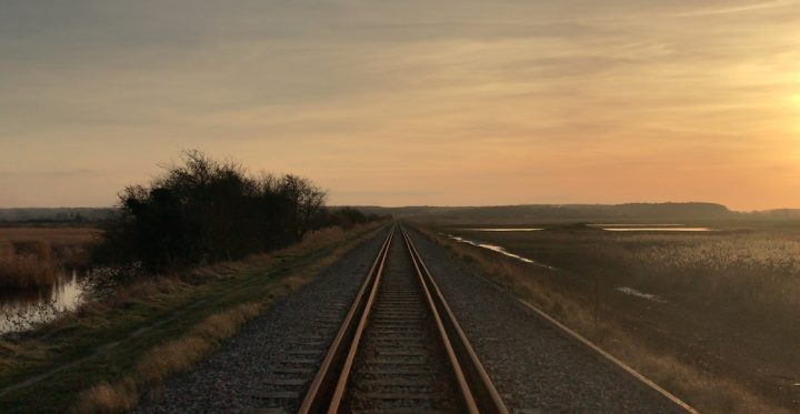 train track in a flat rural location with a pink sky