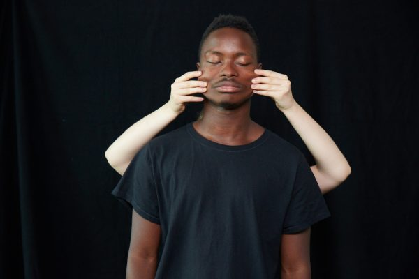 Two people standing with black background. one person standing behind another with arms pulling their face.