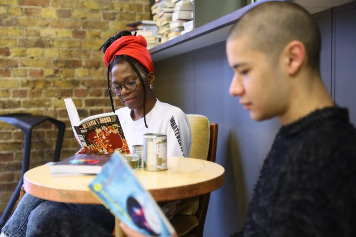 Two people sit at a table reading books