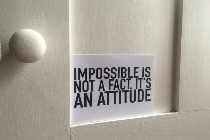 "closer up of white door with handle on left and postcard sitting on a ledge stating ""impossible is not a fact, it is an attitude"""