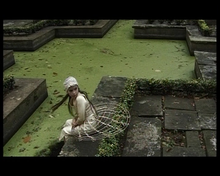 A girl sits with her feet in a pond and turns to look behind her