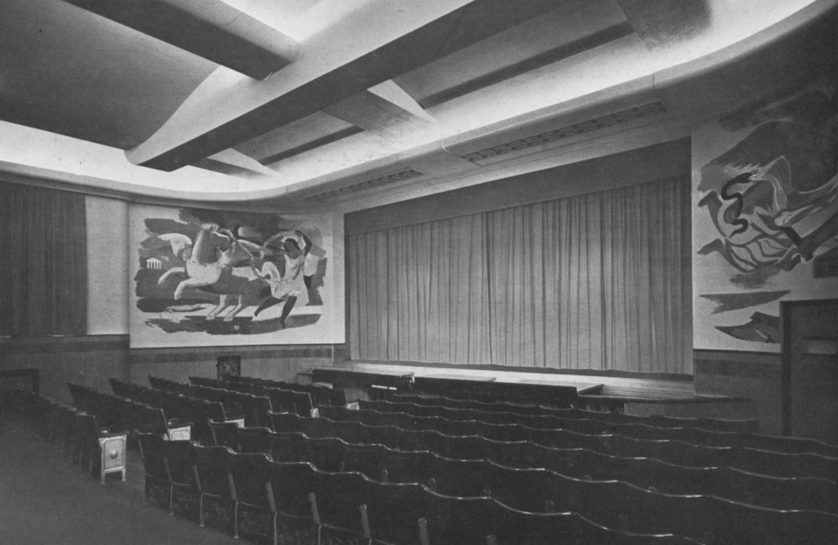 Black and white photo of a theatre with rows of seats, a stage with curtain down and murals on either side of the stage