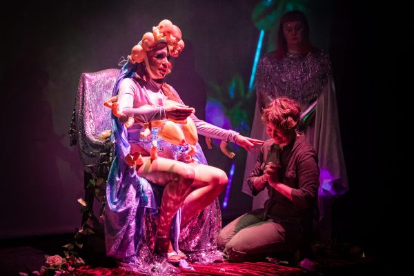 person kneeling by a performer wearing a costume made from plastic dolls in a chair covered in sequins