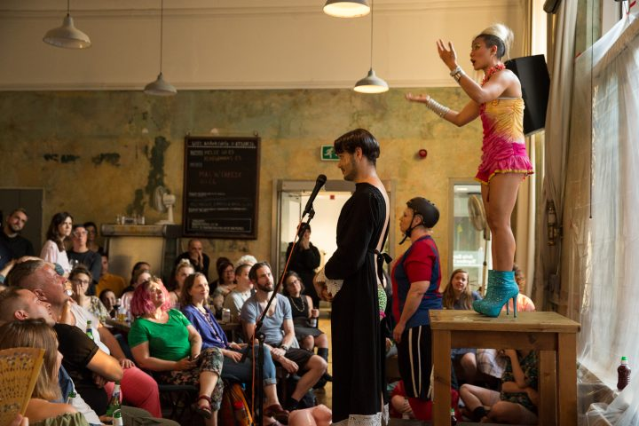 a performer on a table in a cafe filled with people