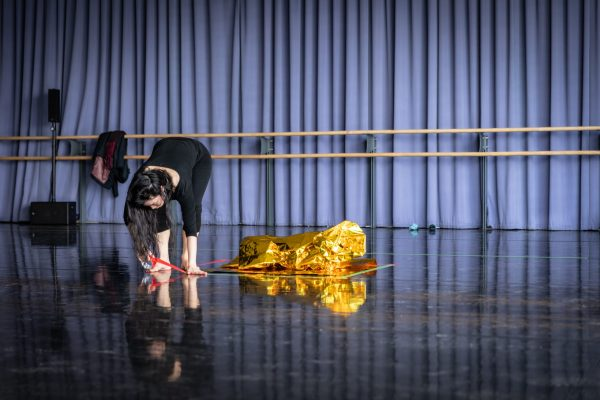 Performer in dance studio putting tape on the floor. There is a gold foil blanket on the floor next to them.