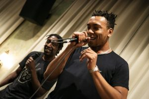 two performer speaking into a mic and smiling