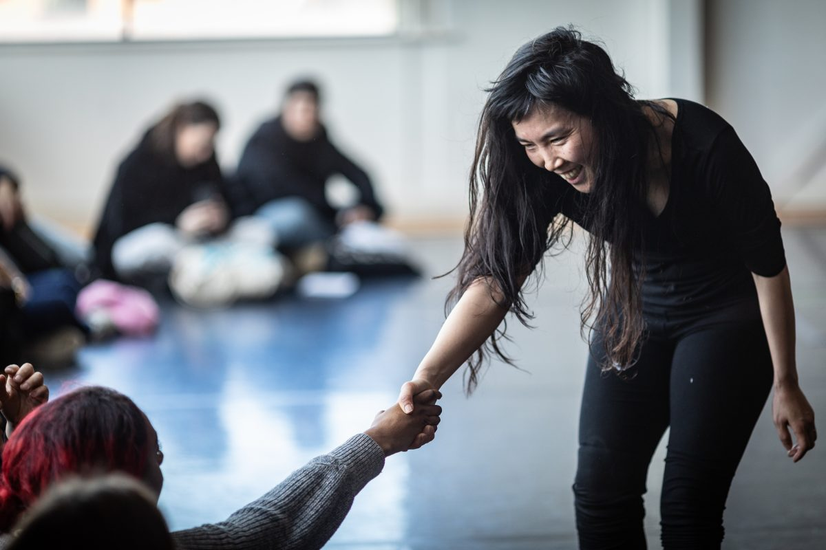 dancer smiling at audience member and holding their hand