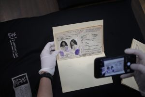 Phone taking a photo of an ID card. The ID card is held by a person wearing white gloves