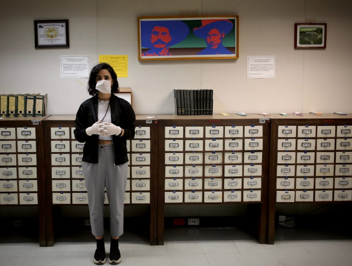 Person wearing mask and gloves stands in archive-like room