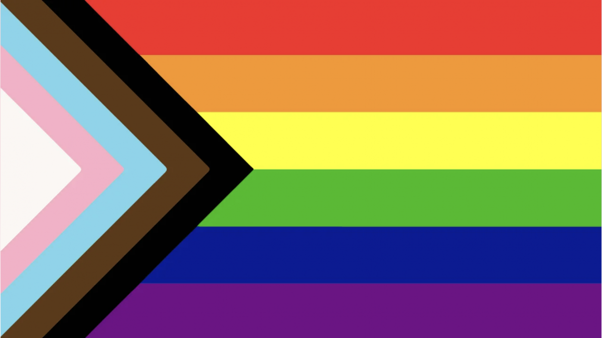 Pride rainbow flag with black and brown stripes to represent marginalised LGBT communities of colour, along with the colours pink, light blue and white, which are used on the Transgender Pride Flag.