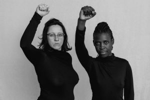 Two people holding their right arm in the air, facing the camera, wearing dark turtle necks against a white backdrop. It is a black and white photograph