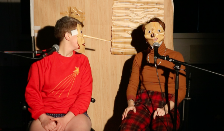 two people sitting on chairs in masks in front of microphones