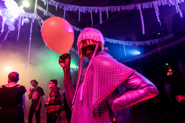 Person holding a ballon in a party and smiling
