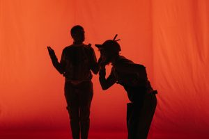 Silhouettes of two people against a red backdrop