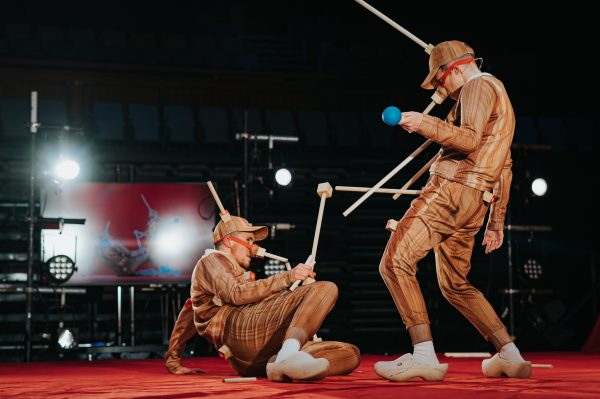 two people with wood textured costumes on and wooden sticks stand and lie on the floor