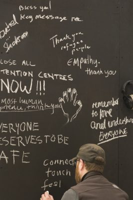 Person writing in white chalk on a blackboard. Writing includes messages like 'thank you refugee people' and 'remember to love and understanding everyone'