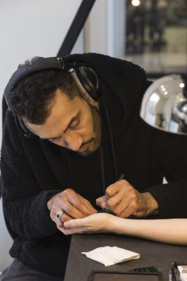 person wearing headphone draws on someone else's hand