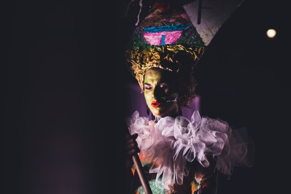 Person in colourful costume and headdress in dark space