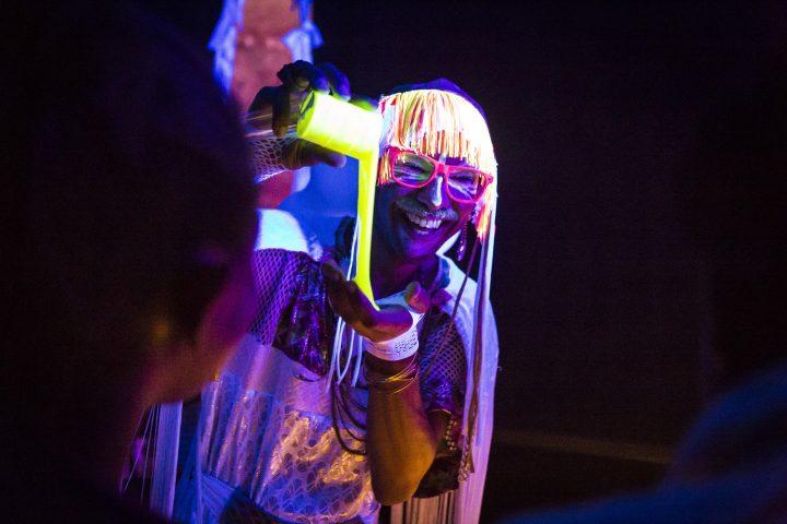 person smiling pouring a fluorescent liquid