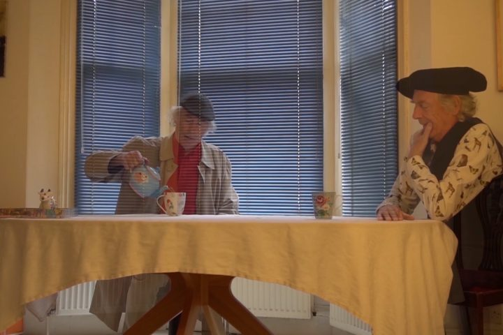 Two versions of the smae person sit with each other at a table drinking tea