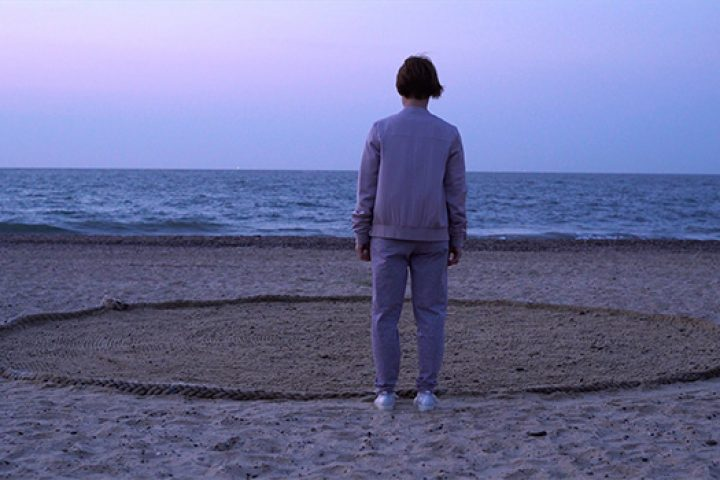 Person stands on a beach facing out to sea with a circle drawn in the sand