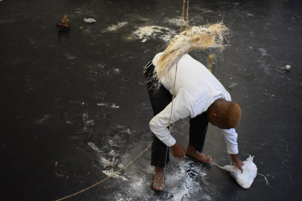 James Jordan Johnson bending over and wiping up flour on the floor with what looks like straw suspended above