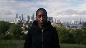 Lady Unchained stared straight of with the city scape of London behind her