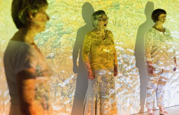 Three people dressed in white, standing and singing with yellow abstract projections on them