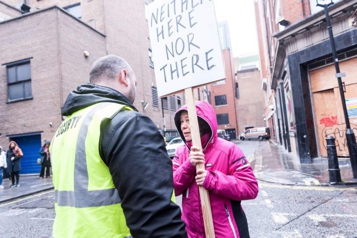 Person in street holding sign saying 'neither here nor there' talking to a taller person in a hi vis jacket