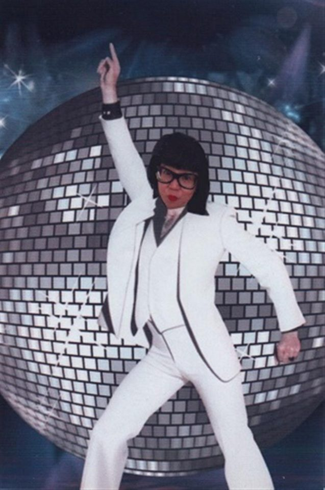 The face of artist Stacy Makishi superimposed on John Travolta in Saturday Night Fever, dancing and wearing a white suit with a large disco ball in the background