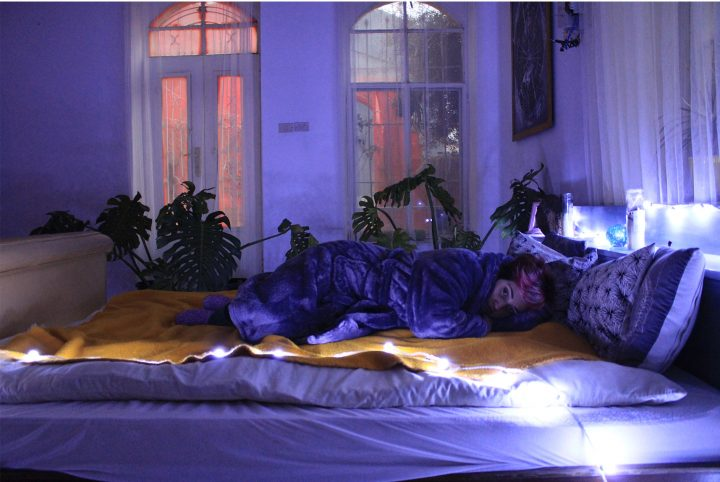 Person lying on a bed in a half-lit bedroom. They are wearing a dressing gown, lying on top of a blanket. There are plants, a large window and a door in the background.