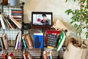 Bookshelves, books, a plant and a screen showing a film of someone talking
