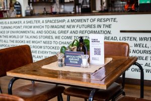 Table in a cafe with a plant, hessian and cards on top. in the background, there is a counter with vinyl signage on it