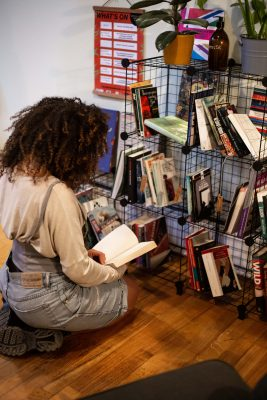 person kneeling and reading a book, next to some bookshelves with plants and books on them