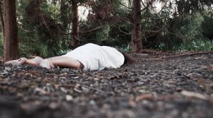 Person lying on the ground in a forest wearing a white gown