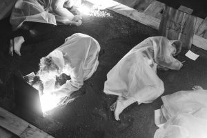 People in white protective suits lying in a dark place on the soil, holding a torch to read something and with their ears to the ground